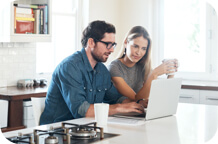 Couple using computer in kitchen