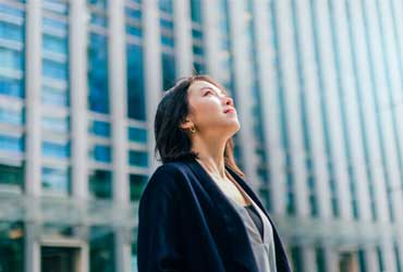 A woman stood outside of an office building looking up