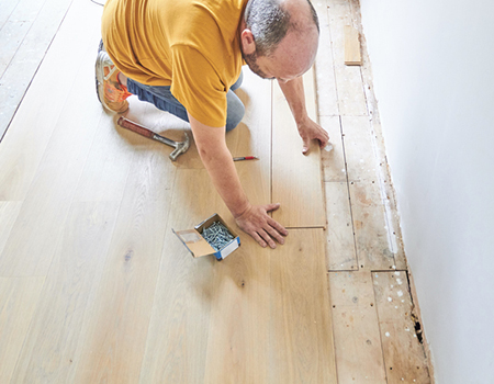 A carpenters laying new wood flooring