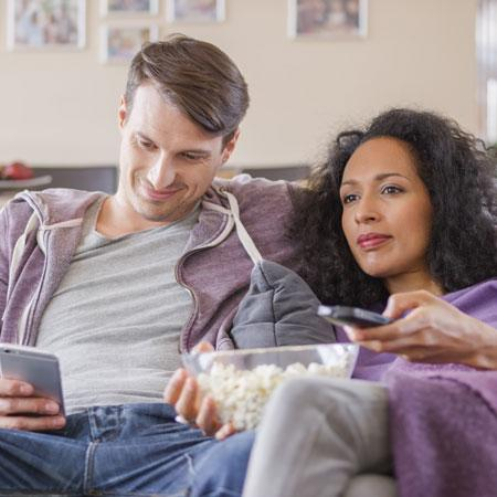 A couple watching TV using their BT TV and Broadband.