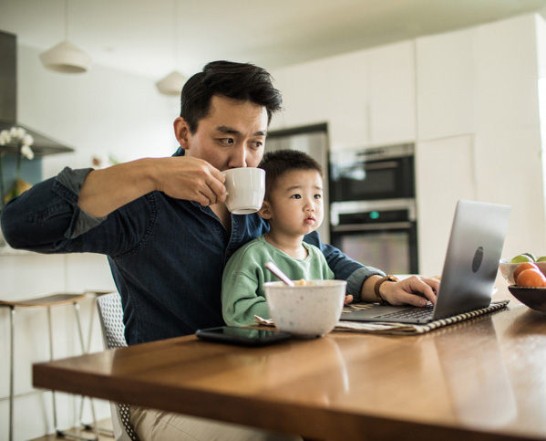 A father and son using a laptop in the kitchen