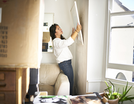 A woman putting up a piece of art in her new home