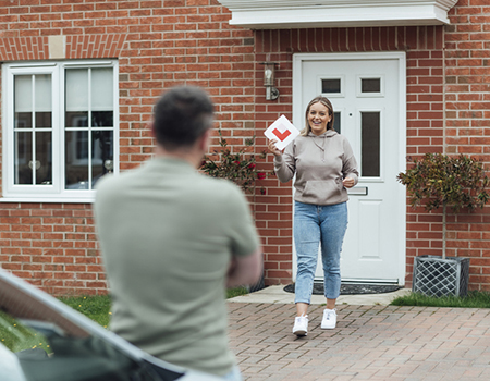A young learner walking out of her house with L plates in hand