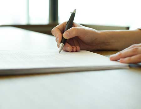 Using a pen to sign a paper