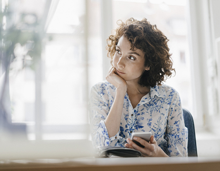Businesswoman in office with smartphone and diary
