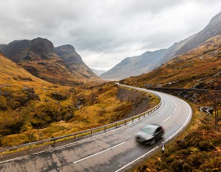 Car driving on scenic road through the mountains