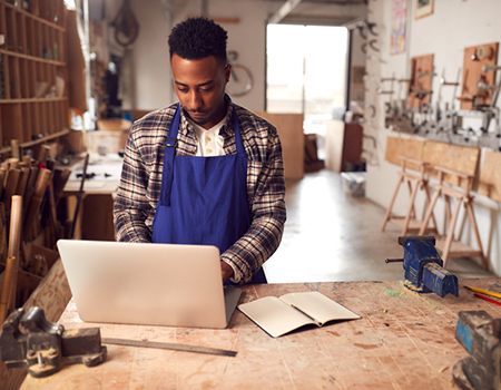 Carpentry business owner working on laptop in workshop