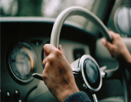 Close up of a persons hands on the steering wheel of classic car