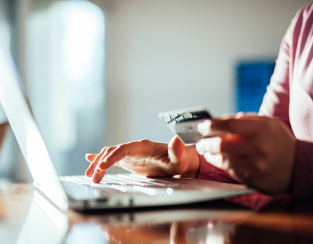 Close up of person using laptop with credit card in hand