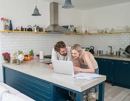 Couple checking credit score in kitchen