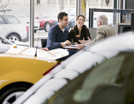 A couple meeting with a car salesman