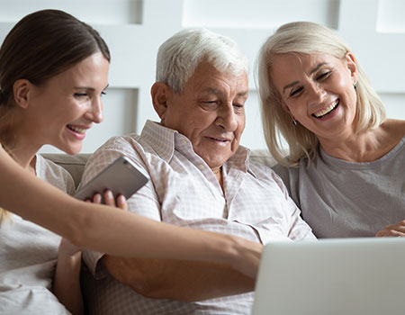 Senior man being shown how to use online banking by daughter and granddaughter