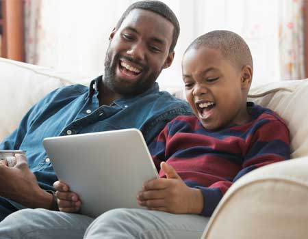 Family laughing looking at a tablet