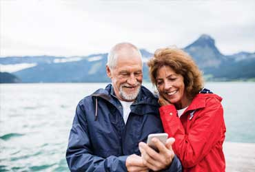 Elderly couple together looking at a phone