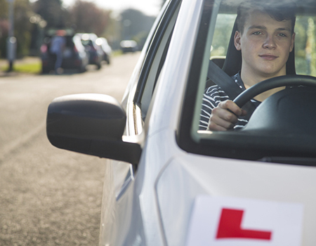 Leaner driver driving a silver car