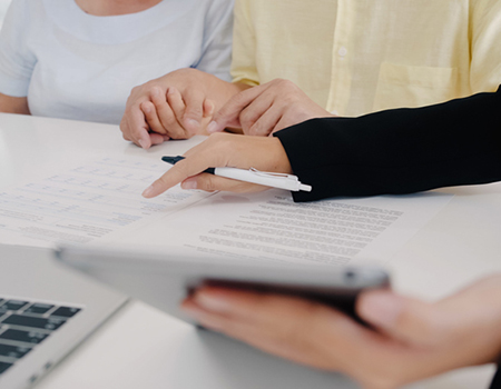 Close up of two people reading Terms and Conditions with an insurance agent