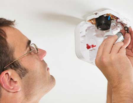 Man changing a battery in a smoke alarm