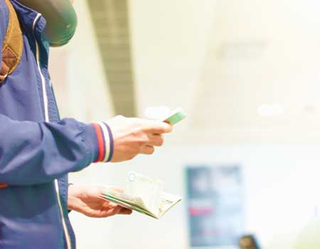 A man holding passport and travel documents in airport