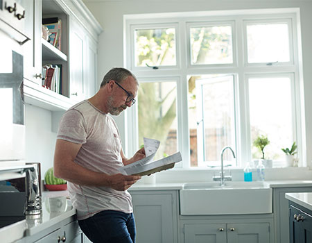Person looking at documents in kitchen at home