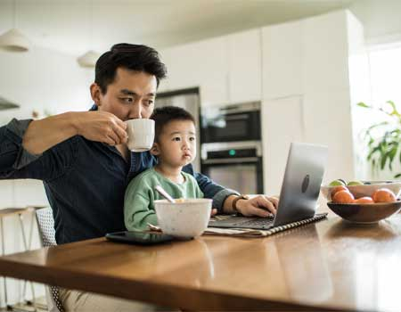 dad and son looking at a laptop
