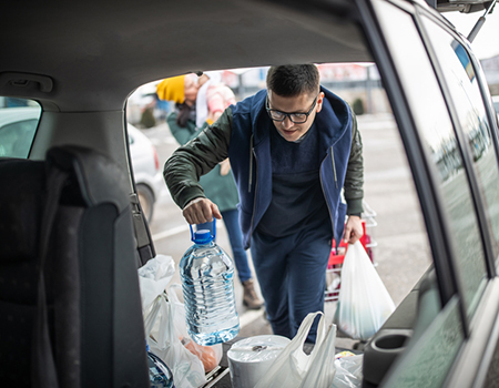 Man loading shopping into boot of car