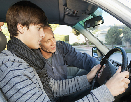 Man supervising a young learner driver