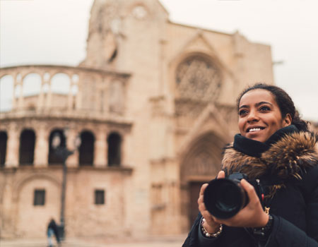 A lady standing visiting a castle and taking pictures using her camera.