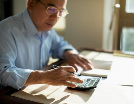 A man working out his mortgage with a calculator