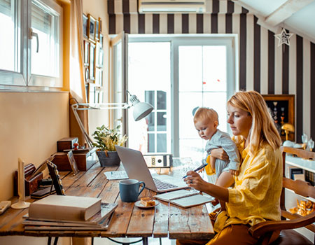Mother using laptop with baby in arms