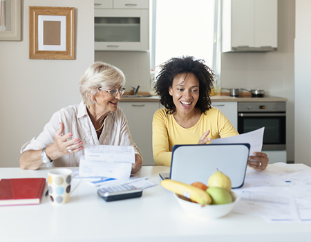 Mother and daughter looking at paperwork together in the kitchen