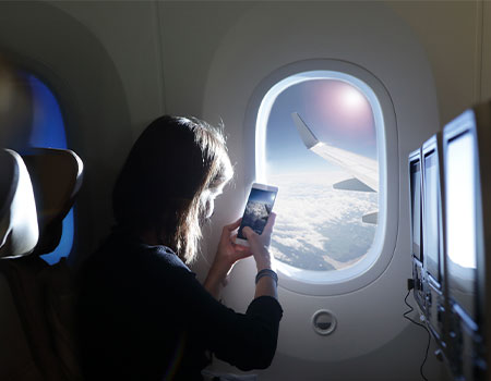 Person taking picture of view from plane window