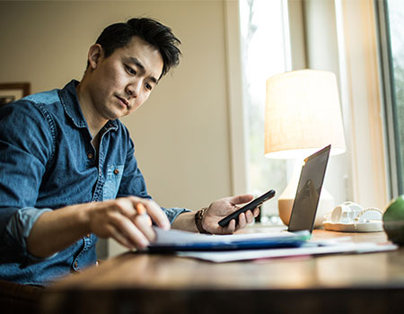 Person using laptop and smartphone in home office