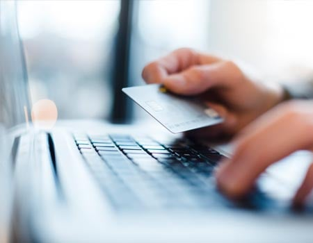 Typing on laptop with credit card in hand