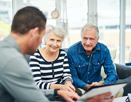 Senior couple having a meeting with financial advisor at home