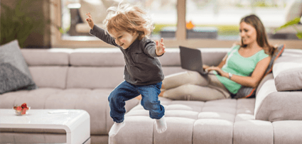 Kid jumping on sofa whilst mother works on laptop