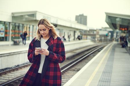 Women on her phone at a train station