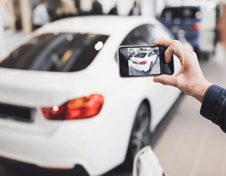 A man taking a picture of his car before he leaves the car rental place. This will ensure that he is not charged for any damages that were already on the car.