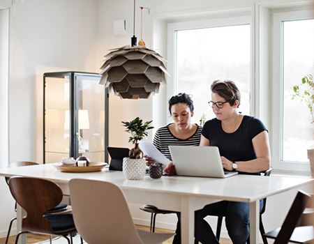 Two people sat at their dining room table looking at a letter in front of a laptop