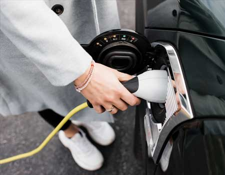 Woman charging up an electric car