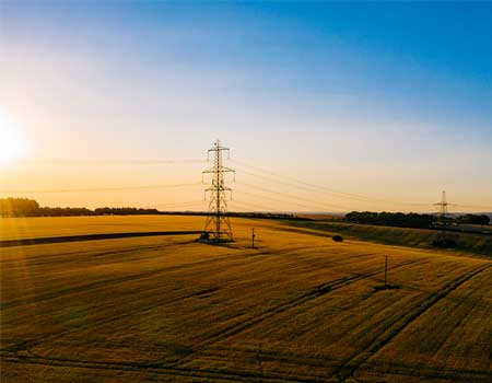 Pylons in a field during sunrise