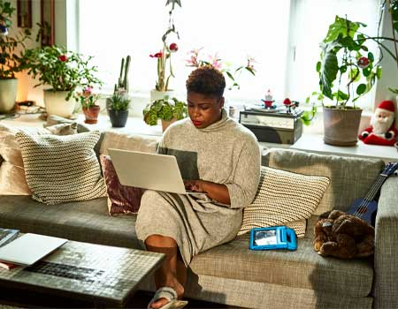 Woman sat on a sofa looking at a laptop