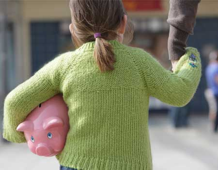 Young girl carrying piggy bank