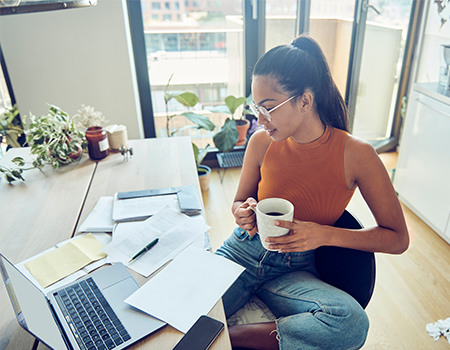 Person working on laptop with paperwork and coffee in hand