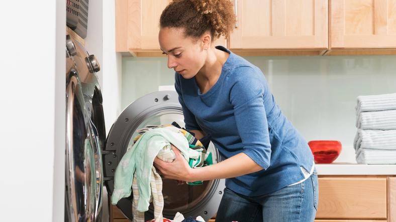 A lady putting her laundry into the washing machine.