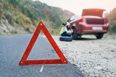 An individual broken down on a road, a warning triangle is in front of the vehicle.