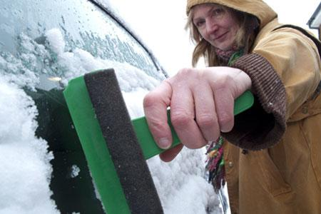 A woman scraping ice from her car