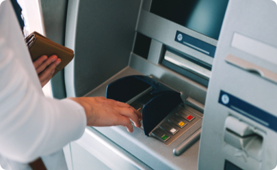 A image of someone withdrawing cash with a travel credit card.