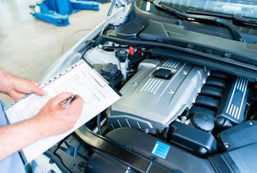 An individual checking a car's engine against a criteria