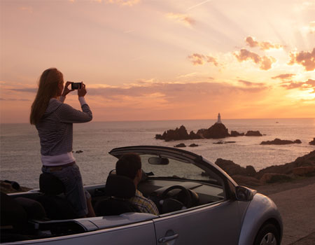 Woman taking picture of view in car on holiday