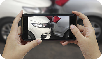 An individual taking a picture of a car crash involving two cars | Compare the Market